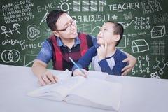 Życzliwy nauczyciel uczy chłopiec w klasie Zdjęcie Stock