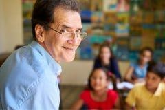 Życzliwy nauczyciel W Klasowym Szczęśliwym profesorze ono Uśmiecha się Przy kamerą fotografia royalty free
