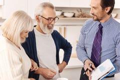 Życzliwy pośrednik handlu nieruchomościami przedstawia kontrakt dla mieszkanie inwestyci klienci Fotografia Stock