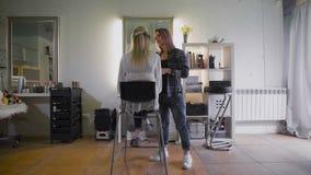 Życzliwy stylista pracuje z jego miarowym klientem w piękno salonie blond atrakcyjna kobieta zbiory wideo