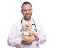 Życzliwy uśmiechnięty paediatrician trzyma misia Fotografia Royalty Free