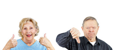 Yea or Nay couple. Senior women giving two thumbs up and grumpy men thumb down Stock Image