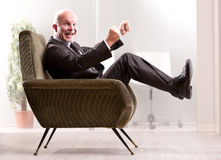 Yeaaaah! I'm in the right business!. Cheering and exulting mature businessman on an armchair in an office laughing and looking at you Stock Photography