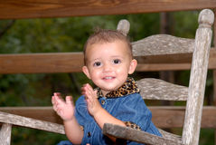 Yeah. A cute little girl sitting in an old rocker clapping her hands outdoors wearing a denim outfit trimmed in leopard print Stock Images