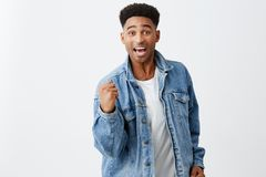 Yeah. Finally. We did it. Cheerful young attractive black-skinned man with afro hairstyle in denim jacket holding hand Royalty Free Stock Images