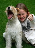 Yeah! thumbs up!. A white caucasian girl child with her puppy showing thumbs up and laughing Stock Photo