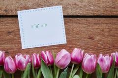 Yeah tulipas da mensagem da mola na madeira Foto de Stock Royalty Free
