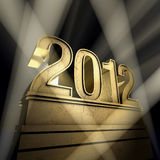 Year 2012. Number 2012 on a golden pedestal at a black background Royalty Free Stock Images