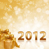 Year 2012 gold sparkling background and gold gift. Year 2012 with abstract gold sparkling background and gold gift boxes Stock Photography