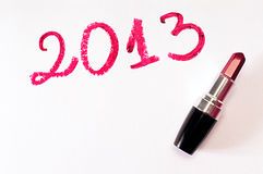 Year 2013 and lipstick. 2013 written with red lipstick on white paper background royalty free stock image