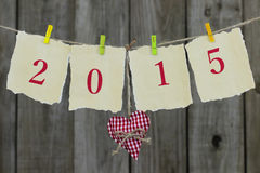 Year 2015 on antique paper with red fabric heart hanging on clothesline by wood fence Royalty Free Stock Image