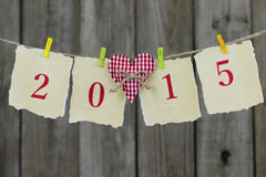 Year 2015 on antique paper with red heart hanging on clothesline by shabby wood fence. 2015 antique parchment paper sign with red gingham heart hanging on Stock Photography