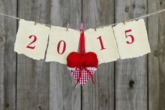 Year 2015 on antique parchment paper hanging on clothesline with red heart by wooden background Stock Images