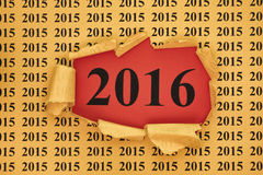 Year 2016 appears through the torn paper with 2015 year Royalty Free Stock Photo