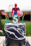 5 year baby birthday cake with spiderman on top ans batman mask on table outdoor.  stock photo