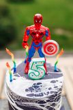 5 year baby birthday cake with spiderman on top ans batman mask on table outdoor.  royalty free stock image