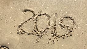 2019 year drawn on the sand being washed away by a wave on the beach.  stock footage