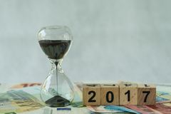Year end 2017 business time countdown as hourglass or sandglass. On pile of Euro banknotes with wooden cube block number 2017 Stock Photography