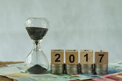 Year end 2017 business time countdown as hourglass or sandglass. On pile of Euro banknotes with wooden cube block number 2017 on stack of coins stock photos