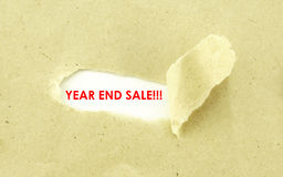 YEAR END SALE. Text YEAR END SALE appearing behind torn light brown envelope Stock Photography