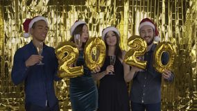 2020 year. falling golden confetti .4 people with golden letters made of foil are dancing on a gold background. red stock video footage