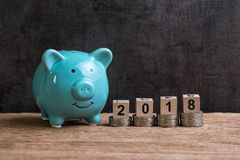 Year 2018 financial goal with piggy bank and stack of coins and. On top by wooden cube block with number 2018 on table and dark black background with copy space Stock Photos