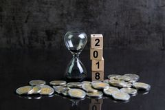Year 2018 financial or investment time or goals concept with hou. Rglass or sandglass and stack of coins and cube block with number 2018 in black theme Stock Photography