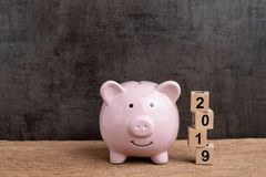 Year 2019 financial target, budget, investment or business goals concept, pink piggy bank and stack of cube wooden block building. Year number 2019 on wood stock photography