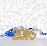 2016 year golden figures and silvery and blue Christmas decorati. 2016 year golden figures on the background of silvery and blue Christmas decorations Royalty Free Stock Photo
