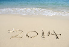 Year 2014 hand written on the white sand Royalty Free Stock Photography