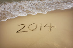 Year 2014 hand written on the white sand i Royalty Free Stock Photography