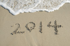 Year 2014 hand written on the white sand i Royalty Free Stock Photos