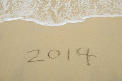 Year 2014 hand written on the white sand i Stock Photography