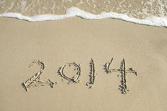 Year 2014 hand written on the white sand i Stock Images