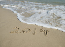 Year 2014 hand written on the white sand i Stock Image