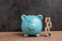 Year 2019 happy saving target, budget, investment or finance goals concept, blue piggy bank and stack of cube wooden block stock image