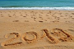2019 YEAR inscription written in the wet yellow beach sand. Concept of celebrating the New Year, party on the shores of the royalty free stock photos