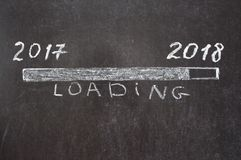Sign loading with 2018 year. 2017 year on the left and 2018 year on the right with sign loading. Hand drawing with chalk on blackboard. Conceptual image Royalty Free Stock Image