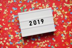 Year 2019 lightbox sign on red paper background with confetti royalty free stock photography