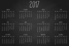Year 2017 monthly calendar. Hand written calendar for the year 2017 over black chalkboard background stock illustration