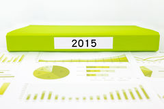 Year number 2015, graphs, charts and business buget planning. Green document binder with year number 2015 place on graphs and charts of business buget planning Royalty Free Stock Images