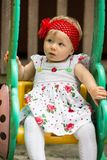 Year-old adorable little child girl  sitting on a swing at summer. Almaty, Kazakhstan Royalty Free Stock Images