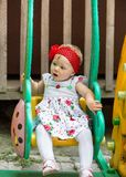 Year-old adorable little child girl  sitting on a swing at summer Royalty Free Stock Image