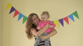1 year old baby girl dancing with mother on her hands on yellow background stock video footage