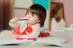 1 year old baby girl drawing with pencils at home. Early learning and education concept stock photos