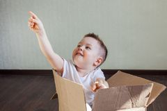 A 4 year old blond boy sits in a box at home and points at something with his finger. A 4 year old blond boy sits in a box at home and points at something with royalty free stock image