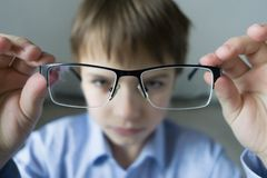 A 9-year-old boy in a blue shirt with glasses checks his eyesight. Dissatisfied with the fact that prescribed glasses - royalty free stock image