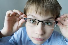 A 9-year-old boy in a blue shirt with glasses checks his eyesight. You should wear glasses. Eye health care royalty free stock photo