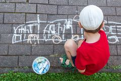 Boy child drawing on pavement royalty free stock photography