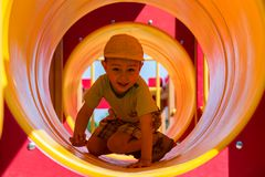 Boy child in tube toy at playground royalty free stock photography